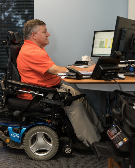 Professional CPA in a wheelchair working.  He has two large screens and a raised desk to make his workstation more accessible.