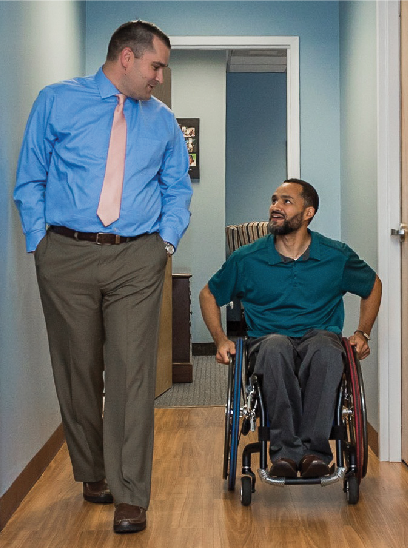 Man walking side-by-side with man in wheelchair discussing an issue.