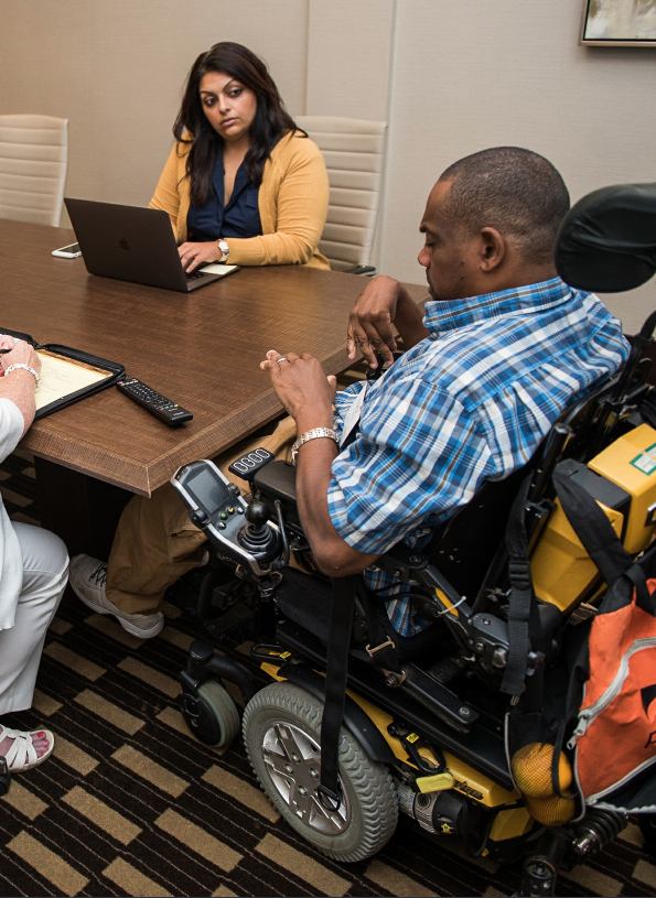 Employee with disabilities in wheelchair leading group discussion.